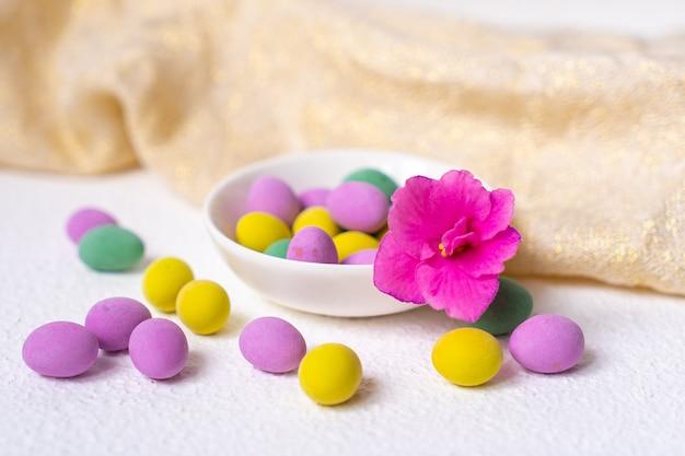 Oeufs de pâques colorés et fleur avec plaque sur un bureau blanc. vue de dessus, horizontale. affiche, maquette pour la conception. mise au point sélective