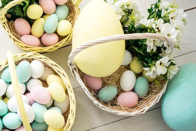 Oeufs de pâques colorés et fleurs dans des paniers en osier. espace copie - concept de pâques