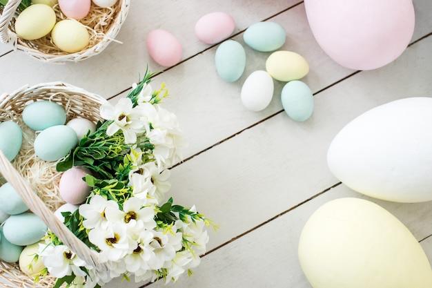 Oeufs de pâques colorés et fleurs dans des paniers en osier