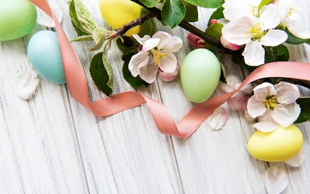 Oeufs de pâques colorés avec des fleurs de printemps sur fond de bois.