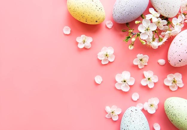 Oeufs de pâques colorés avec des fleurs de printemps sur fond rose.