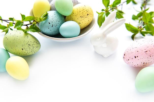 Oeufs de pâques colorés avec des fleurs de printemps isolé sur fond blanc.