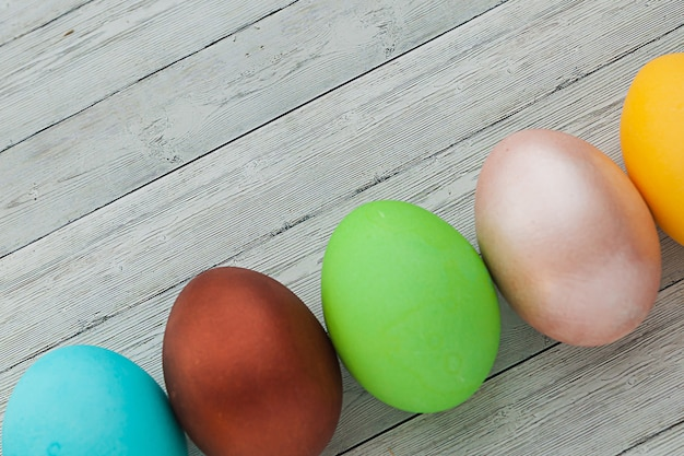 Oeufs de pâques colorés sur un fond en bois clair.