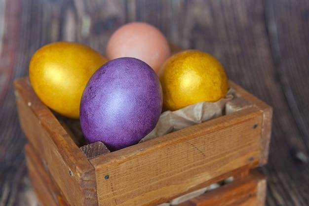 Oeufs de pâques colorés sur fond en bois foncé.