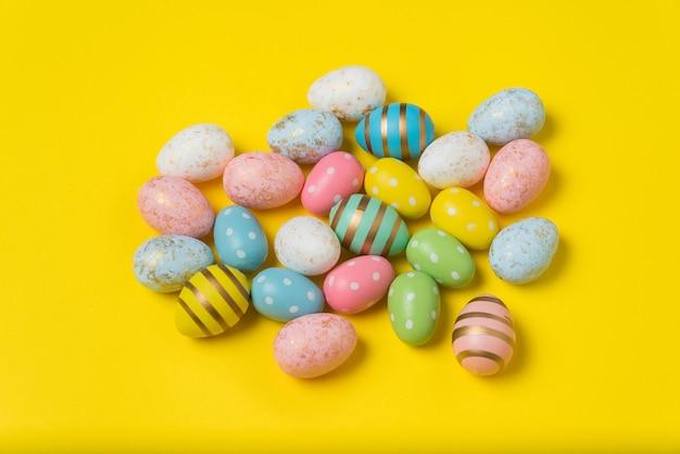 Oeufs de pâques colorés sur fond jaune vif. oeufs festifs multicolores.