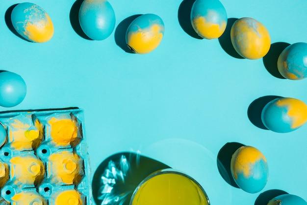 Oeufs de pâques colorés avec une grille et un verre d'eau