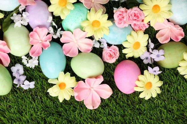 Oeufs de pâques colorés sur l'herbe avec fond de fleurs