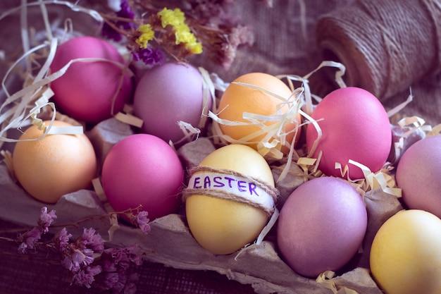 Oeufs de pâques colorés avec inscription «pâques» dans un nid