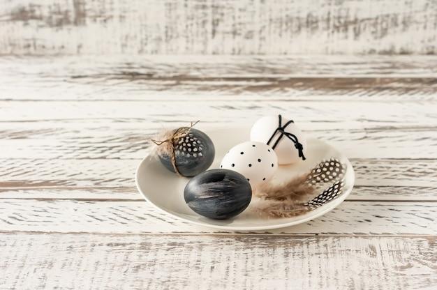 Oeufs de pâques colorés à la mode dans des couleurs sombres et des plumes sur une assiette sur une table en bois. préparation des vacances de pâques. composition festive.