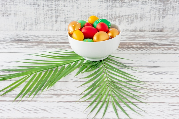 Oeufs de pâques colorés à la mode, feuilles tropicales vertes et plumes sur une assiette sur une table en bois. préparation des vacances de pâques. composition festive
