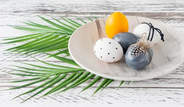Oeufs de pâques colorés à la mode, feuilles tropicales vertes et plumes sur une assiette sur une table en bois. préparation des vacances de pâques. composition festive.