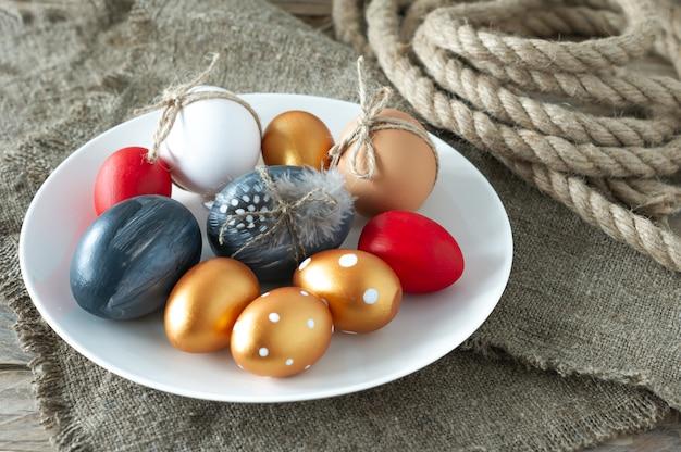 Oeufs de pâques colorés à la mode, toile et corde et plumes sur une assiette sur une table en bois. préparation des vacances de pâques. composition festive.