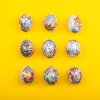 Oeufs de pâques colorés peints en produits naturels bleuets et pelures d'oignon, isolés sur une surface jaune
