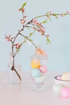 Oeufs de pâques colorés près de rameau de fleurs dans un vase avec de l'eau et un bol