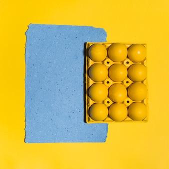 Oeufs de pâques colorés en rack avec une feuille de papier sur la table