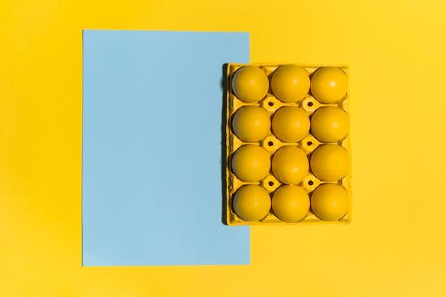 Oeufs de pâques colorés en rack avec une feuille de papier vierge sur la table