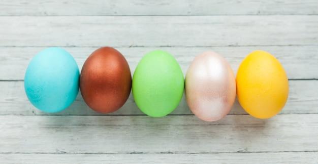 Oeufs de pâques colorés sur une surface en bois clair