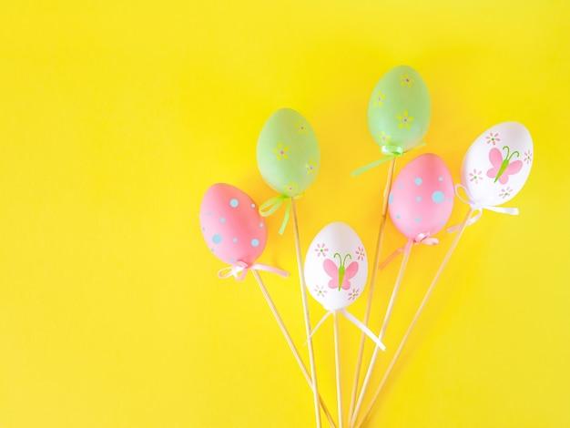 Oeufs de pâques colorés suspendus sur des rubans et des bâtons isolés sur fond jaune