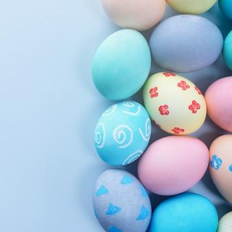 Oeufs de pâques colorés teints par de l'eau colorée avec un beau motif sur fond bleu pâle, concept de design d'activité de vacances, vue de dessus, espace de copie.