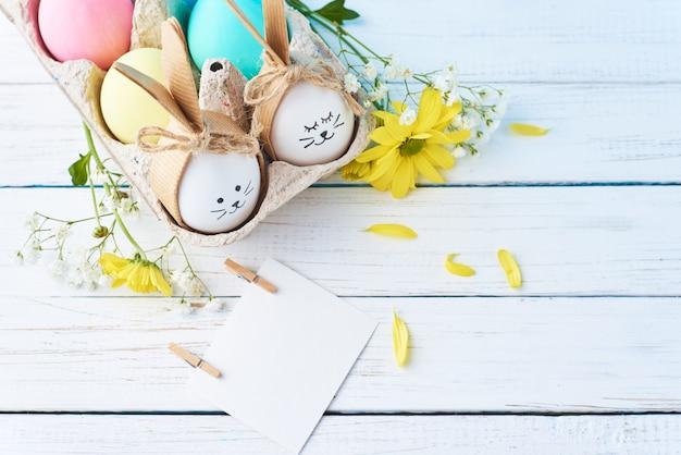 Oeufs de pâques colorés avec des visages peints dans un bac à papier avec decorationd sur fond blanc