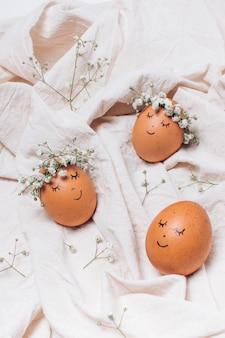 Oeufs de pâques avec des couronnes de fleurs décoratives entre textile