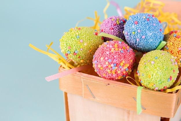 Oeufs de pâques dans la boîte de dessin animé d'oeuf sur fond bleu se bouchent. décorations festives.