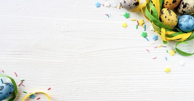 Oeufs de pâques dans un nid décoratif sur fond de bois blanc