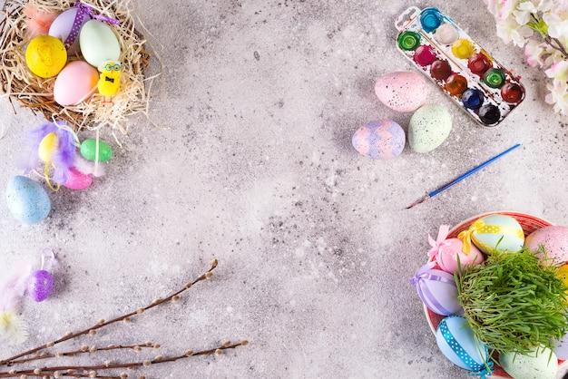 Oeufs de pâques dans un nid d'herbe, biscuits glacés faits maison et peintures pour peindre des œufs et de l'herbe