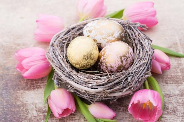 Oeufs de pâques dans le nid avec des tulipes autour