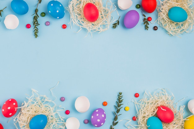 Oeufs de pâques dans des nids avec des branches de plantes et des bonbons