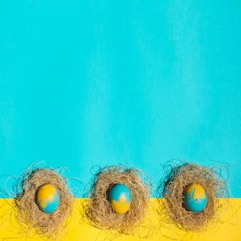 Oeufs de pâques dans les nids sur la table bleue