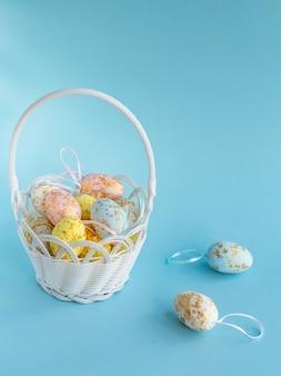 Oeufs De Pâques Dans Un Panier Blanc Sur Une Surface Bleue .décoration De Pâques Heureuse. Orientation Verticale. Photo Premium
