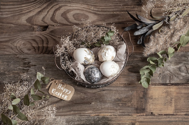 Oeufs de pâques dans un panier décoratif avec des fleurs séchées sur une table en bois. joyeuses pâques.