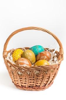 Oeufs de pâques dans un panier marron sur blanc