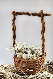 Oeufs de pâques dans un panier en osier décoré de fleurs blanches.