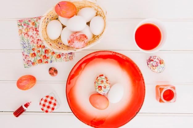 Oeufs de pâques dans le panier près d'une assiette, une serviette et une tasse de liquide colorant