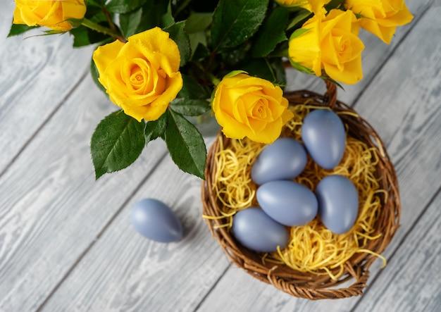 Oeufs de pâques dans le panier et roses jaunes vu de dessus