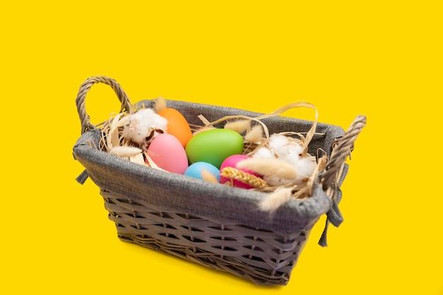 Oeufs de pâques dans le panier sur la surface jaune