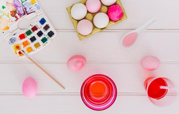 Oeufs de pâques dans un récipient entre des tasses de liquide de teinture près de cuillères et un pinceau avec un ensemble de couleurs