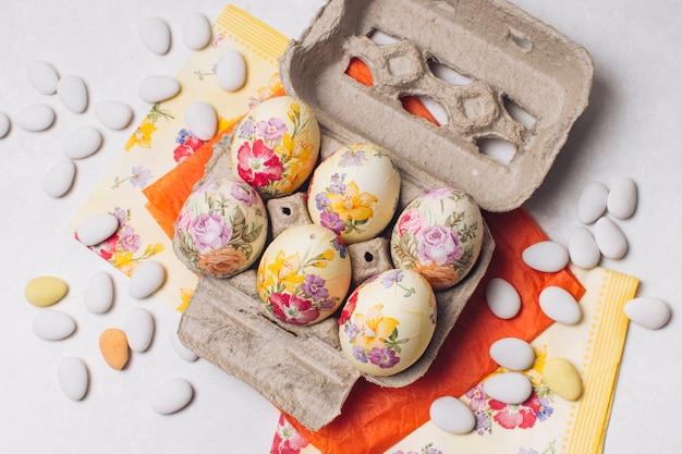 Oeufs de pâques dans un récipient près de serviettes et de petites pierres