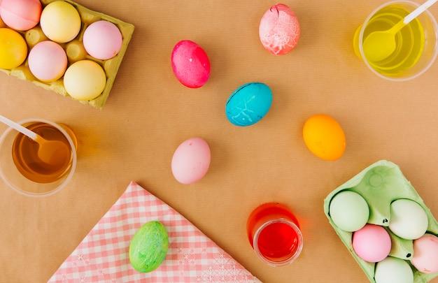 Oeufs de pâques dans des récipients près de tasses avec liquide de teinture coloré et serviette