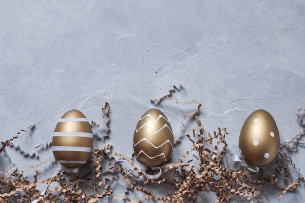 Oeufs de pâques décoratifs de couleur or avec un motif et un décor en papier gris