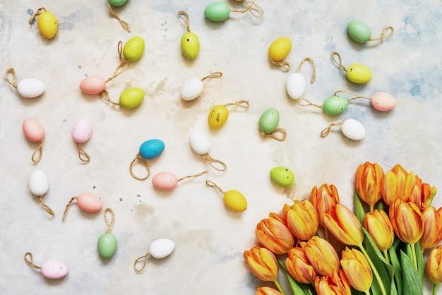 Oeufs de pâques décoratifs et tulipes de printemps sur fond coloré. copiez l'espace, vue de dessus. mise à plat du concept de célébration de pâques.