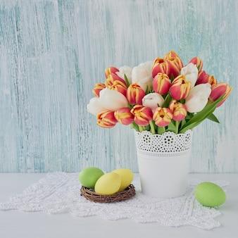 Oeufs de pâques décoratifs et tulipes rouges dans un vase. copier l'espace