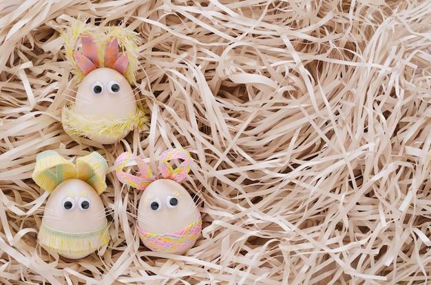 Les oeufs de pâques décorent comme un lapin sur nid en papier