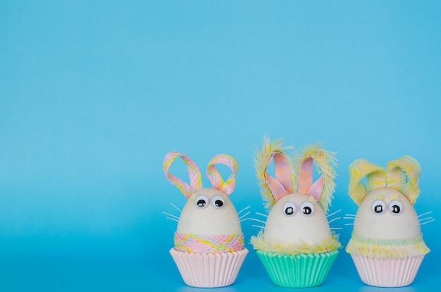 Oeufs de pâques décorer comme lapin sur une tasse en papier cupcake coloré