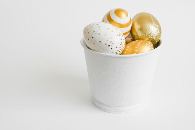 Oeufs de pâques décorés doré dans un seau sur fond blanc