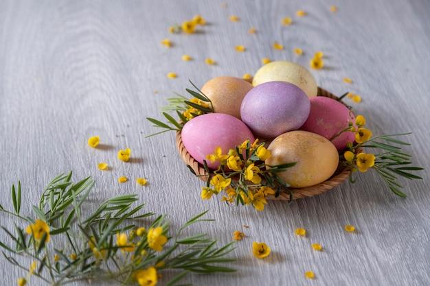 Oeufs de pâques décorés de fleurs jaunes sur une table en bois