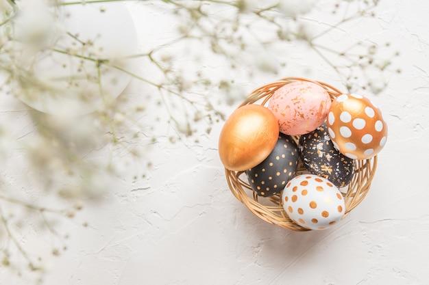 Oeufs de pâques décorés en noir, blanc et doré dans un panier en osier décoré de gypsophile sur fond de béton blanc