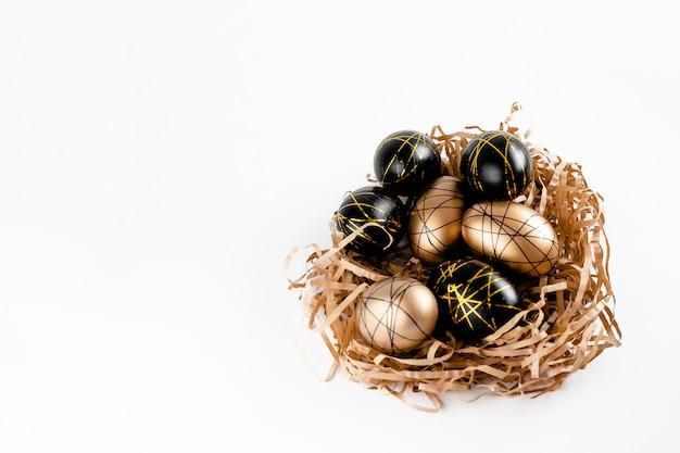 Oeufs de pâques décorés d'or dans le nid sur fond blanc. espace de copie de concept de pâques minimal pour le texte. vue horizontale de dessus, flatlay.